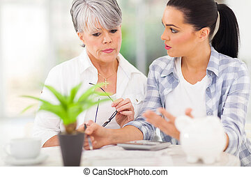 adult daughter helping senior mother with her finances