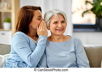adult daughter whispering to senior mother at home