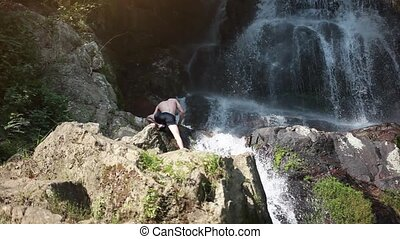 Adult extreme man descending a waterfall on Koh Samui....