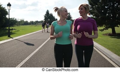Adult female joggers pursuing activity outdoors - Two...