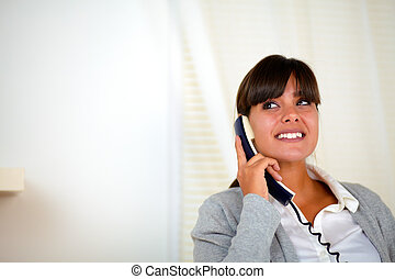 Adult female looking up and speaking on phone