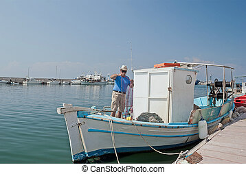 Adult fisherman on white traditional boat in Greece