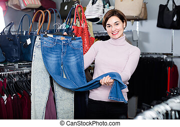 Adult girl deciding on new jeans