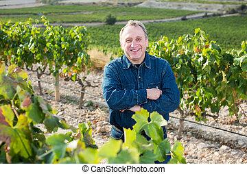 Adult glad man standing on vineyard