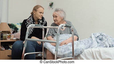 Adult granddaughter visiting elderly grandma in the hospital