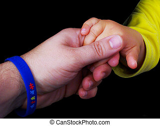 adult hand with an autism awareness wrist band holding an autistic baby hand