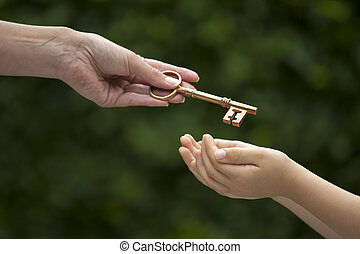 adult hands key to child - mother handing key to daughter