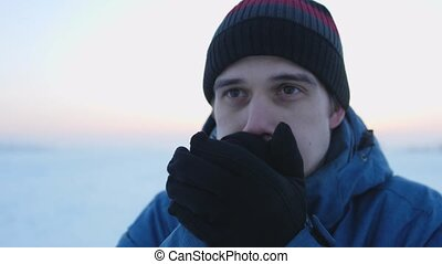 Close up portrait of adult handsome caucasian man in winter clothes standing outside freezing rubbing hands