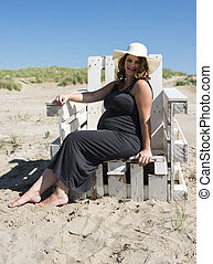 pregnant woman sitting on wooden chair on the beach