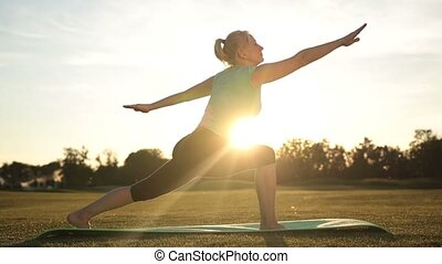 Adult healthy woman practicing yoga at sunset