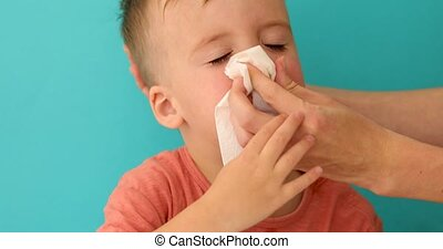 Adult helps child to blow and wipe his running nose - Adult...