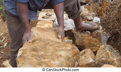 Adult indian human cutting blocks of granites with hammer...