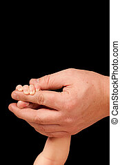 Adult is holdint infant hand on black background