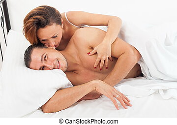 Adult lovers kissing in bed