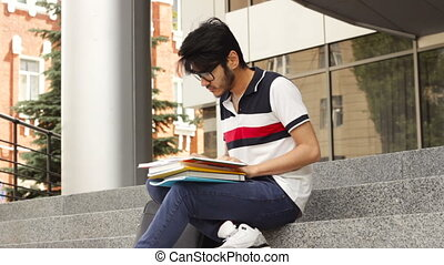 Adult male asian student sitting on stairs and reading book...