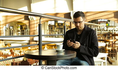 Adult male drinking coffee with a phone in his hand in cafes