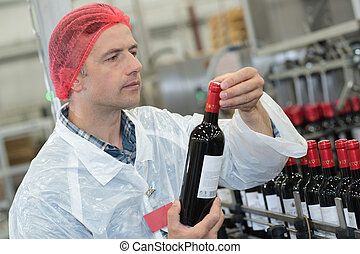 adult male holding newly produced bottle of wine