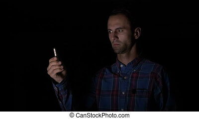 Adult male in shirt using facial recognition in a dark room...