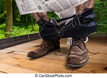 Adult male reading newspaper while sitting on the toilet seat