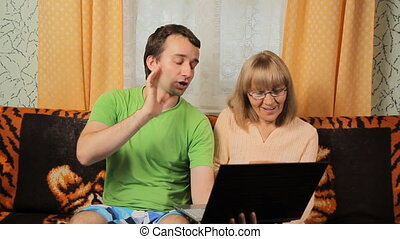 Adult male teaches old woman making video call on laptop. Mother and son smiling and sitting on a sofa at home