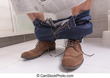 Adult male wearing jeans and shoes reading newspaper while sitting on the toilet seat at home