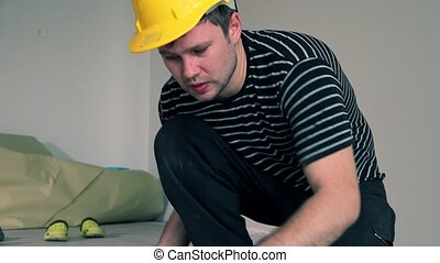 Adult male worker installing laminate floor, floating wooden...