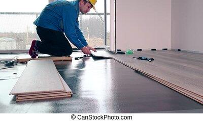 Adult male worker installing laminate floor, floating wood...