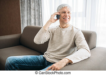 Adult man at home talking by mobile phone