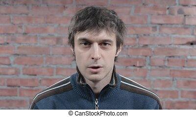 Adult man calmly speak looking on camera. Brick wall...
