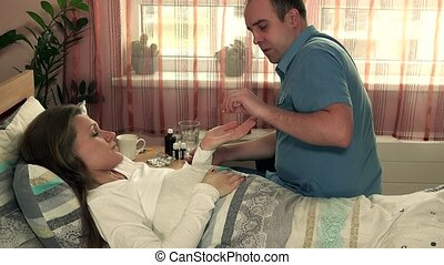 Adult man caring for sick woman. male nurse give pill to ill patient