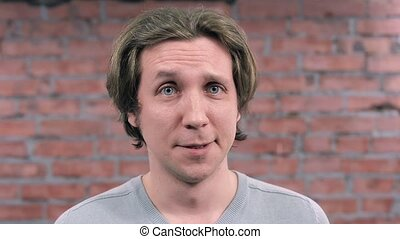 Adult man depict disapproval on camera. Brick wall on background. Audition