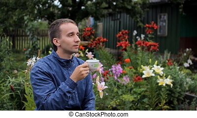 Adult man drinks morning coffee in garden, summer day....