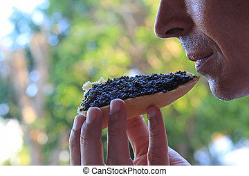 man eating a sandwich with black caviar