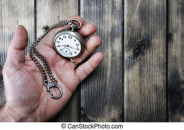 Adult man holding an antique pocket watch in his hand