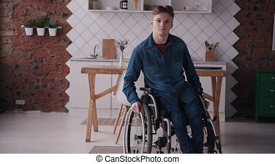 Adult man in sitting wheelchair at cozy house - Young and...