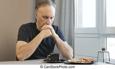 Adult man in the morning in the kitchen, thinking about their problems. He is drinking coffee