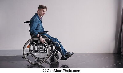 Adult man in wheelchair looking at camera sitting at home -...