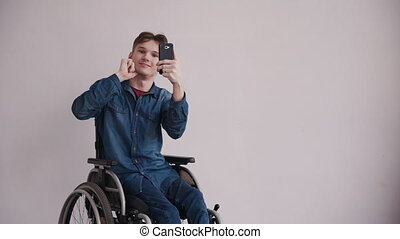 Adult man in wheelchair using cellular phone at home - Adult...