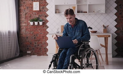 Adult man in wheelchair using modern laptop at home - Adult...