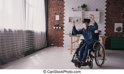 Adult man in wheelchair using virtual reality glasses and interf