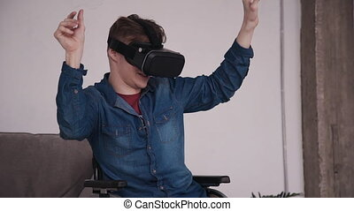 Adult man in wheelchair using virtual reality glasses and...