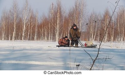 Adult man in winter clothes carrying passenger in the...