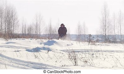 Adult man in winter clothing fast riding and jumping on a...