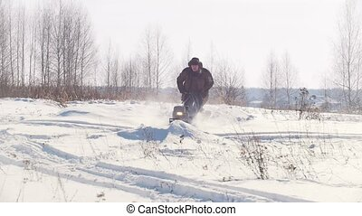Adult man in winter clothing fast riding through the deep...