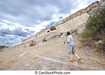 Adult man is hiking with trekking poles