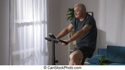 adult man is losing weight, training on exercycle in home, sport activity at self-isolation at pandemic, healthy lifestyle