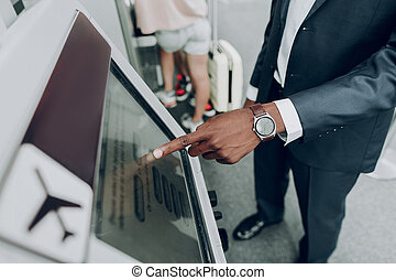 Adult man is using ATM machine at airport