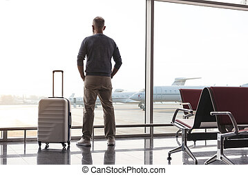 Adult man looking at window of airport