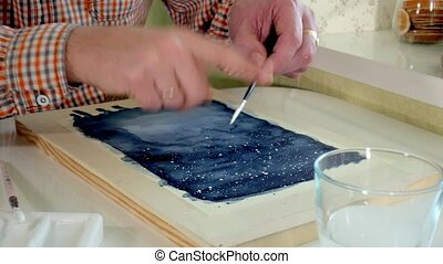 Adult man paint with colored watercolor paints in an home...