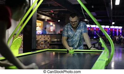 Adult man playing air hockey game